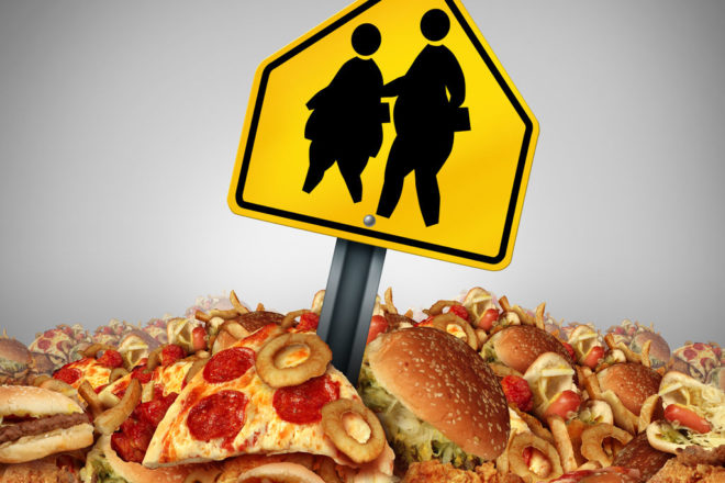 Children Diet Problems And Obesity Crisis In The School Concept As A Heap Of Unhealthy Fast Food With Two Overweight Fat Kids On A A Crossing Traffic