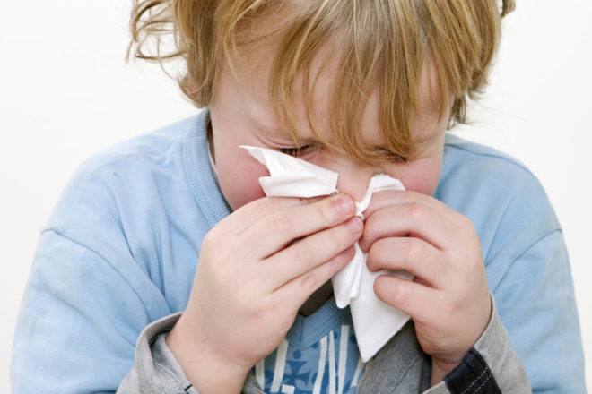 Young Boy Sneezing In A Handkerchief Square Close Up